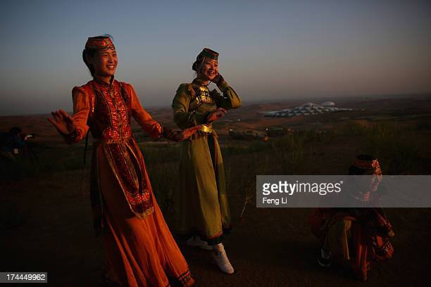 Dancers in traditional costumes attend the Mongolian ritual ceremony near Desert Lotus Hotel in Xiangshawan Desert also called Sounding Sand Desert...