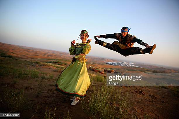 Dancers in traditional costumes perform near Desert Lotus Hotel in Xiangshawan Desert, also called Sounding Sand Desert on July 19, 2013 in Ordos of...