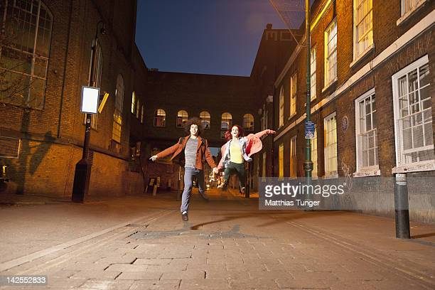 Dancers jumping on a road between brick-houses
