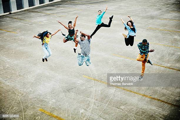 Dancers jumping together in mid-air on rooftop