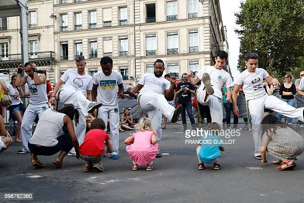 Dancers of the Bahia Sud band perform Capoeira during the Brazilian Cultural Festtival 'Lavage de la Madeleine' on September 2 2016 in front of the...