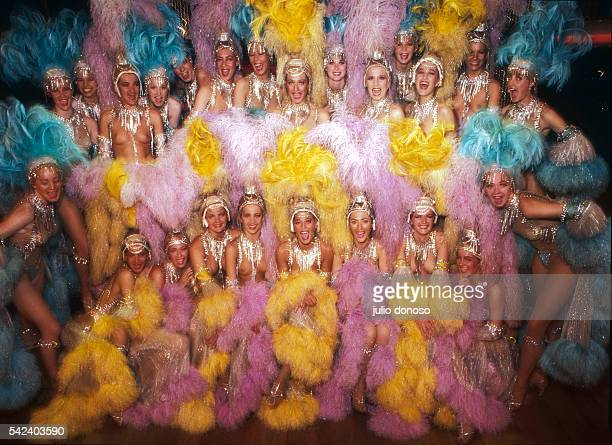 Dancers of the Moulin Rouge pose together in their colorful feathered costumes