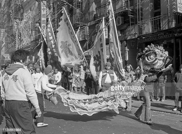 Dancers perform a traditional Lion Dance while others carry large banners and flags during the annual Chinese New Year celebrations on Mott Street in...