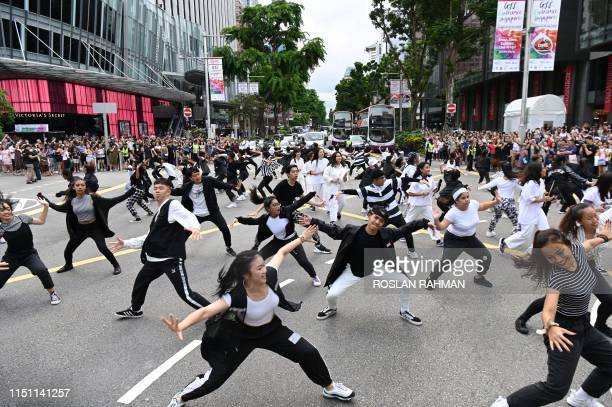 """Dancers perform along the traffic junction of Orchard Road during the launch of the """"Great Singapore Sale"""" in Singapore on June 21, 2019."""
