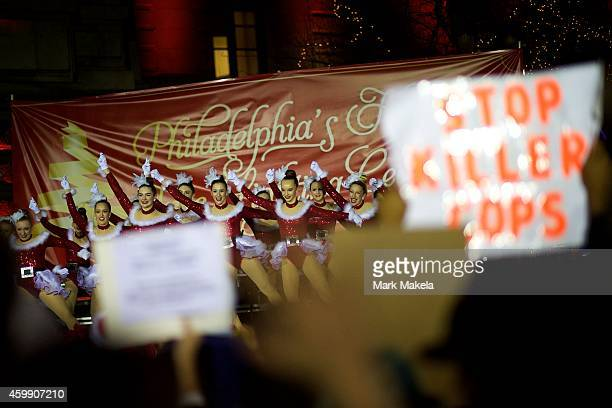 Dancers perform during a Christmas Tree lighting ceremony at City Hall in Philadelphia Pennsylvania while demonstrators gathered there to protest the...