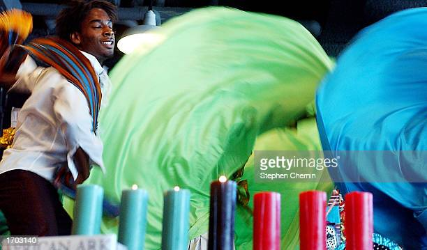 Dancers perform in back of Kwanzaa candles during a Kwanzaa festival at the Museum of Natural History December 28 2002 in New York City Kwanzaa...