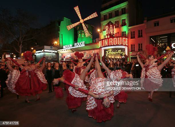 Dancers perform in front of the Moulin Rouge cabaret in the Montmartre neighbourhood in Paris on March 16 as it illuminated in green on the eve of...