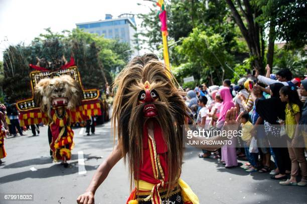 Dancers perform the traditional Reog Ponorogo dance during a street parade in Surabaya on May 7 2017 The parade is part of celebrations to mark the...
