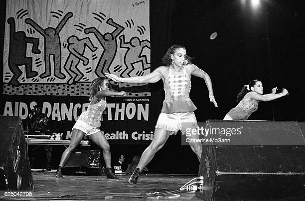 Dancers perform with PM Dawn before a Keith Haring banner at AIDS DanceaThon on November 30th 1991 at Rosalind Ballroom in New York City New York