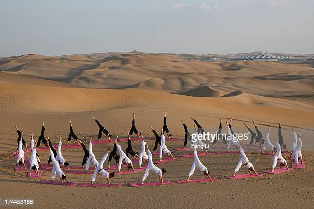 Dancers perform yoga on the dunes of Xiangshawan Desert also called Sounding Sand Desert on July 20 2013 in Ordos of Inner Mongolia Autonomous Region...