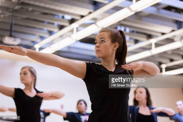 dancers practicing with arms outstretched in rehearsal - teen cheerleader stock photos and pictures
