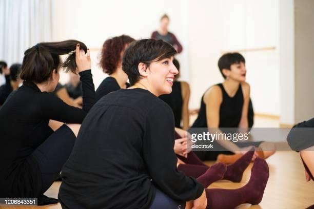 tänzer sitzen und plaudern in einer pause - tanztruppe stock-fotos und bilder