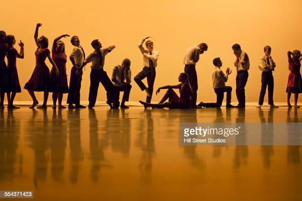 Dancers stretching in rehearsal on stage