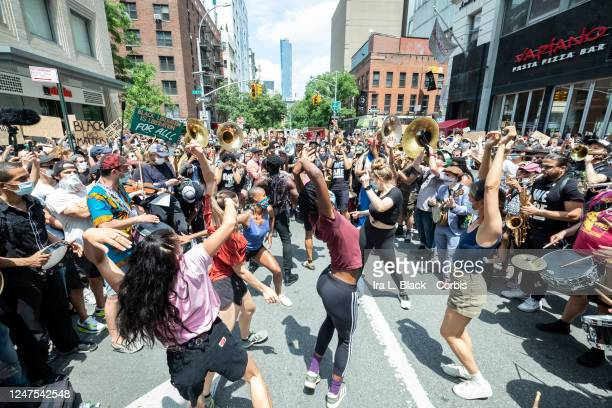 Dancers take the rhythm from Musician Jon Batiste and his band jams for the crowd of people that have followed him onto to 6th Avenue from Union...