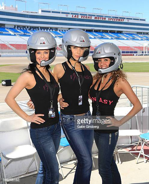 Dancers Tracey Gittins Kristin Ratatori entertainer Lorena Peril from the show 'Fantasy' pose in helmets at the American Muscle Car Challenge by...