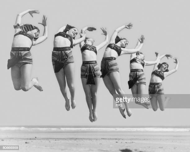 Dancers wearing Egyptian style costumes rehearsing on the beach circa 1930