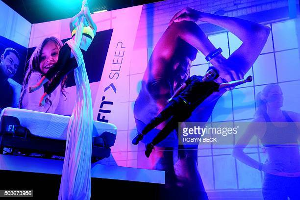 Dancers wearing iFit monitors fly through the air in a performance at the iFit booth January 6 2016 on the first day of the CES 2016 Consumer...