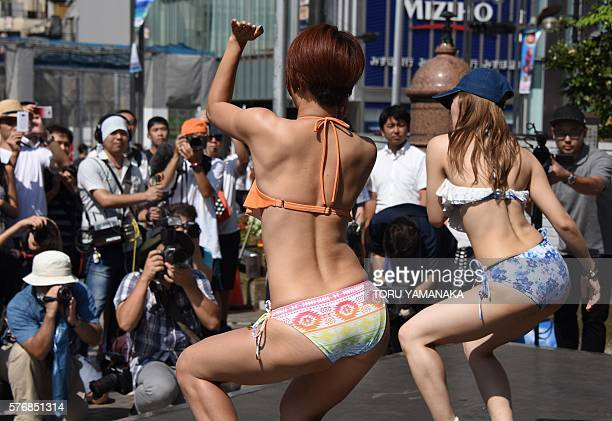 Dancers wearing new bikinis perform in front of passersby and a line of photographers during a promotional flash mob event on a square outside...