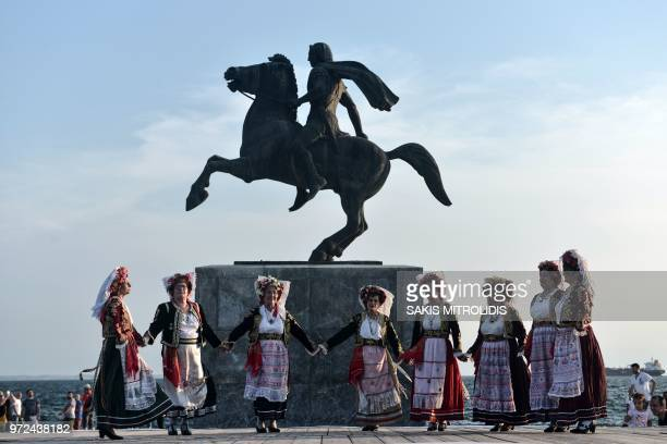 TOPSHOT Dancers wearing traditional costumes performs in front of the statue of Alexander III of Macedon commonly known as Alexander the Great in...