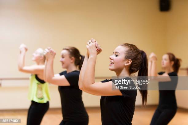 dancers with hands clasped rehearsing in studio - teen cheerleader stock photos and pictures
