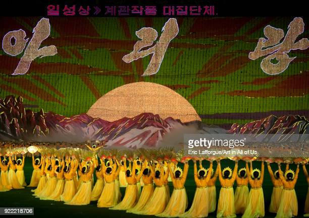 Dancers women in chosonot in front of a giant sun on mount Paektu made by human pixels holding up colored boards during Arirang mass games Pyongan...