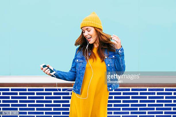Dancing and singing young woman wearing yellow cap and dress
