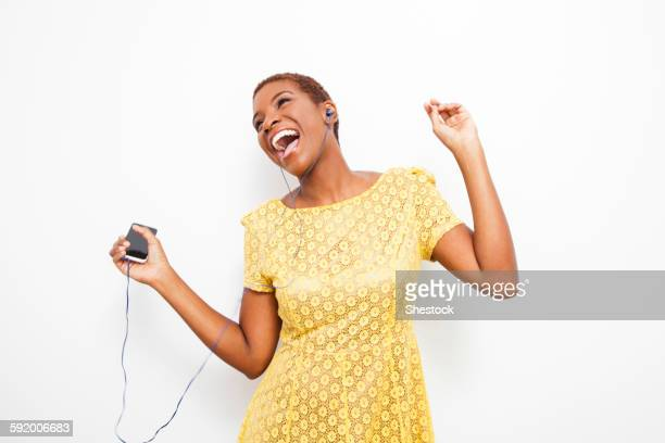 dancing black woman dancing to mp3 player - yellow dress stock pictures, royalty-free photos & images