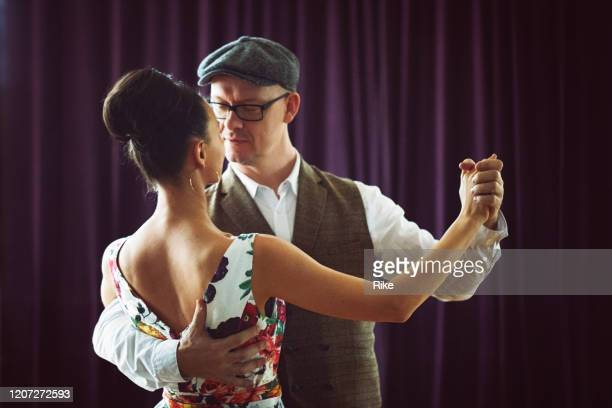 dancing couple in the light dance hall - duet stock pictures, royalty-free photos & images