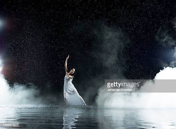 Dancing female in water, rainy and misty night