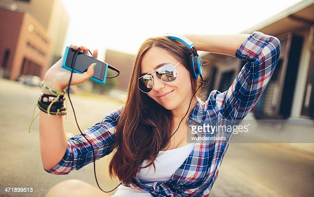 Dancing hipster girl with headphones in city during summer