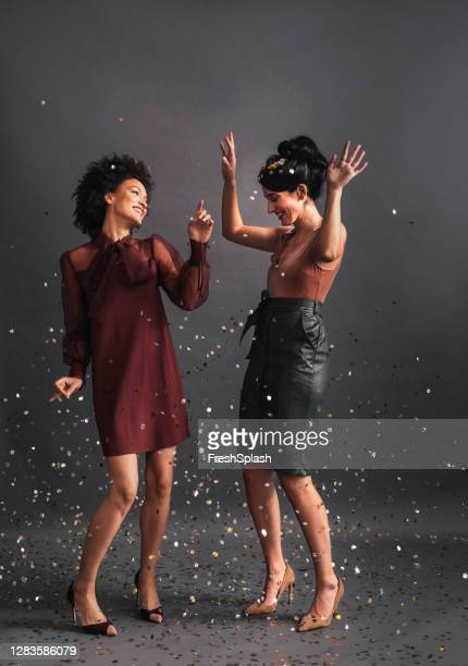 dancing in confetti: two elegant women dancing together at a party (studio shot, copy space) - gray dress stock pictures, royalty-free photos & images