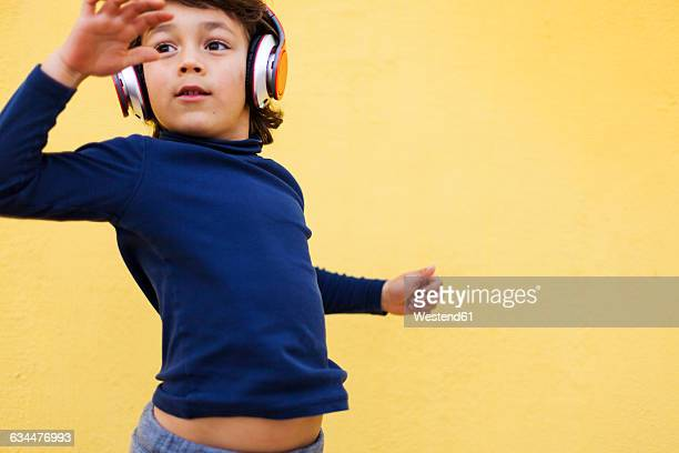 Dancing little boy in front of yellow wall hearing music with headphones