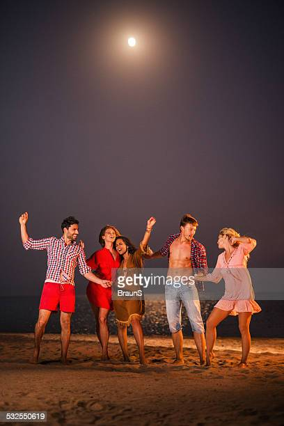 Dancing on a beach party at night.