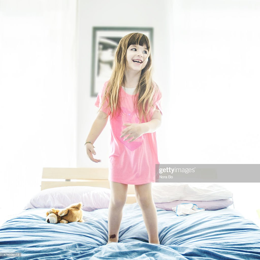 Dancing on parent's bed : Stock Photo