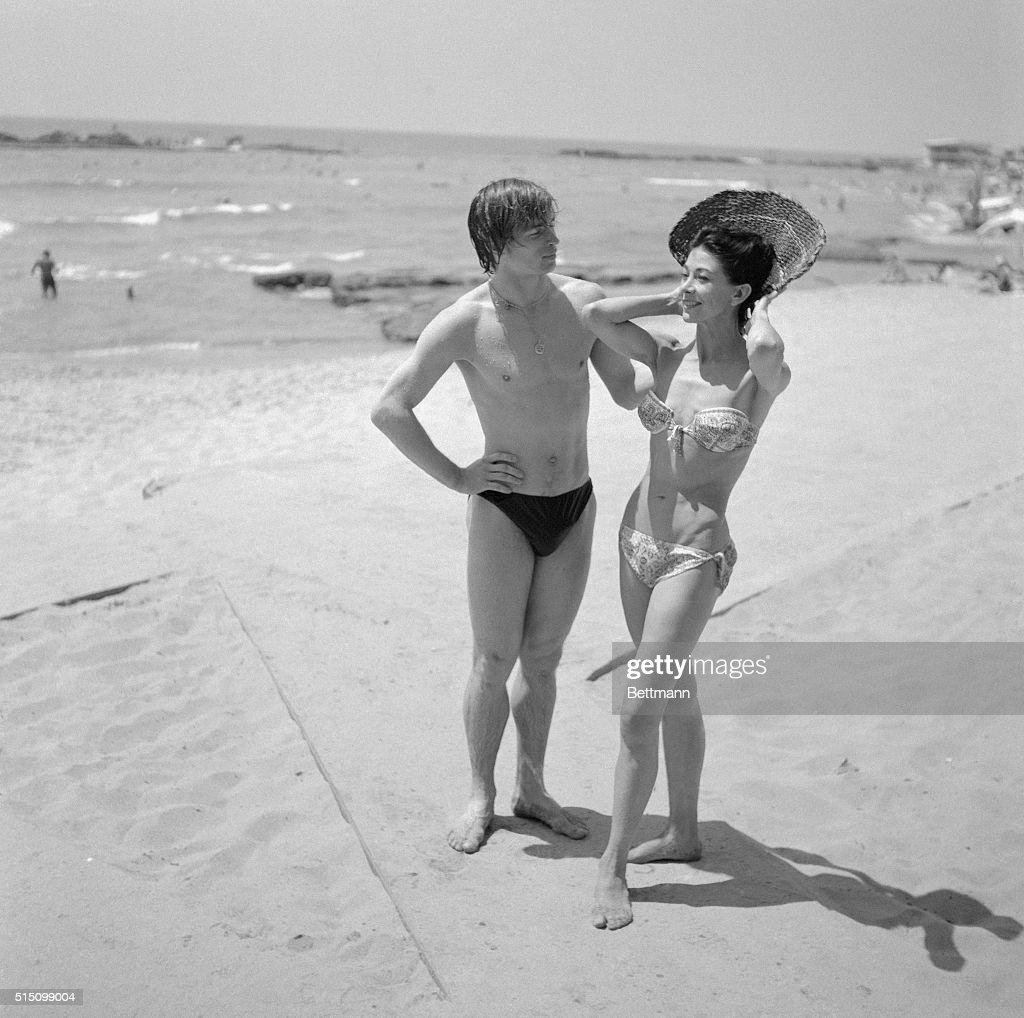 Dancing partners, Dame Margot Fonteyn, prima ballerina of the Royal Ballet, and Soviet dancing star Rudolf Nureyev, who defected from Russia, strike a pose on the beach as they enjoy the sun on the San Simon Beach near Beirut. The dancing couple took time out for swimming and sunning between their performances at the Baalbeck Festival.
