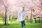 Dancing, running and whirling in beautiful park with cherry trees in bloom