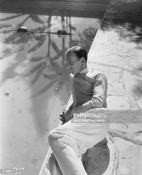 Dancing star Fred Astaire relaxes by the side of a pool