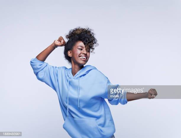 dancing young woman in blue hoodie - izusek stock pictures, royalty-free photos & images