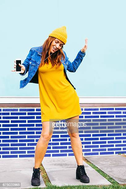 dancing young woman wearing yellow cap and dress - yellow dress stock pictures, royalty-free photos & images