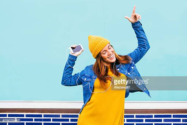 Dancing young woman wearing yellow cap and dress