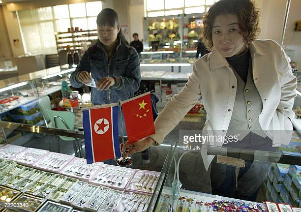 Local vendor places the flags of China and North Korea on the counter at the Memorial Hall of the War to Resist the US Aggression and Aid Korea in...