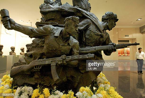 Local visitor walks near a sculpture featuring the soldiers of the Chinese People's Volunteers at the Memorial Hall of the War to Resist the US...
