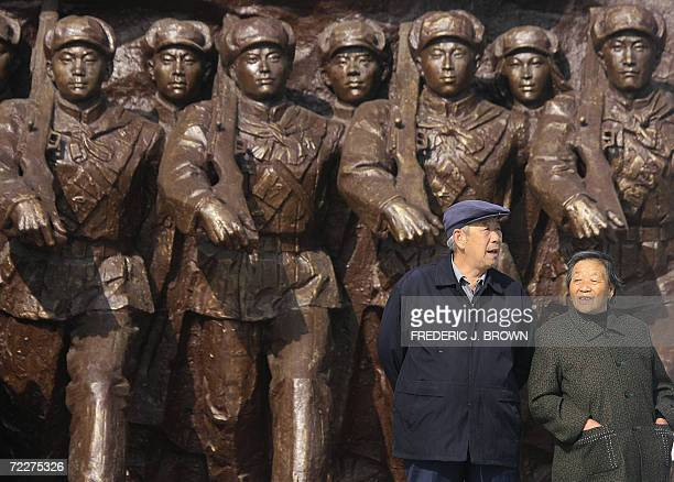 An elderly Chinese couple walk past a monument dedicated to Chinese war heroes of the Korean War , 23 October 2006 in Dandong, in northeast China's...