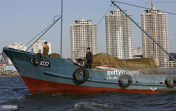 North Koreans stand onboard a ship in the Yalu River in the North Korean town of Sinuiji opposite Chinese border city of Dandong 20 October 2006 US...