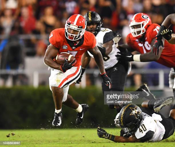 DAndre Swift of the Georgia Bulldogs carries the ball against Jordan Griffin of the Vanderbilt Commodores on October 6 2018 at Sanford Stadium in...
