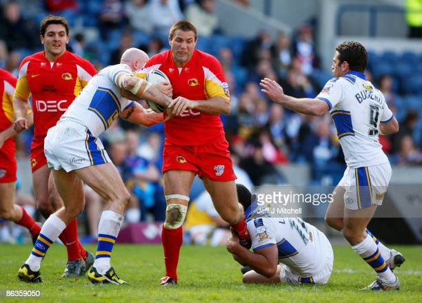 Dane Carlaw of Catalans is wrapped up by the Leeds defence during the Super League Magic Weekend match between Catalans Dragons and Leed Rhinos at...