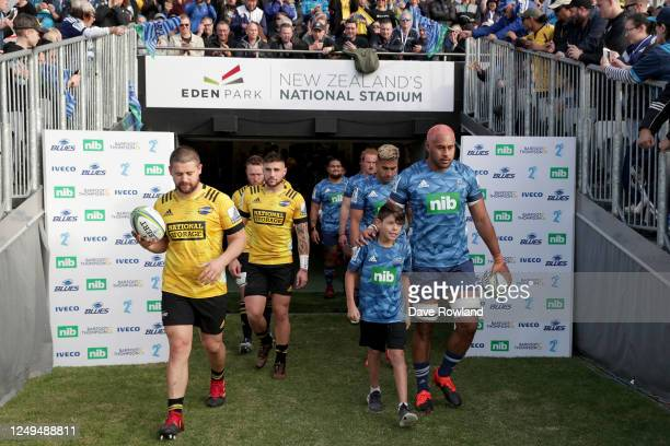 Dane Coles of the Hurricanes and Captain Patrick Tuipulotu of the Blues with ball runner Finn Palmer walk out for the round 1 Super Rugby Aotearoa...