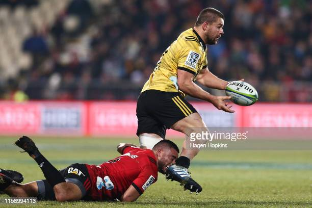 Dane Coles of the Hurricanes looks to pass in the tackle of Bryn Hall of the Crusaders during the Super Rugby Semi Final between the Crusaders and...
