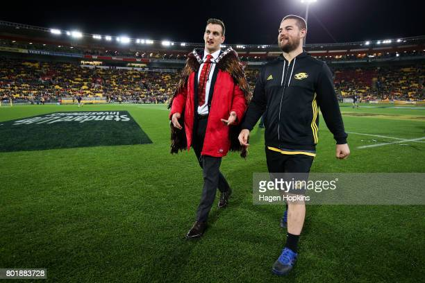 Dane Coles of the Hurricanes talks to Sam Warburton of the Lions after presenting him with at feathered Maori cloak or Korowai during the match...