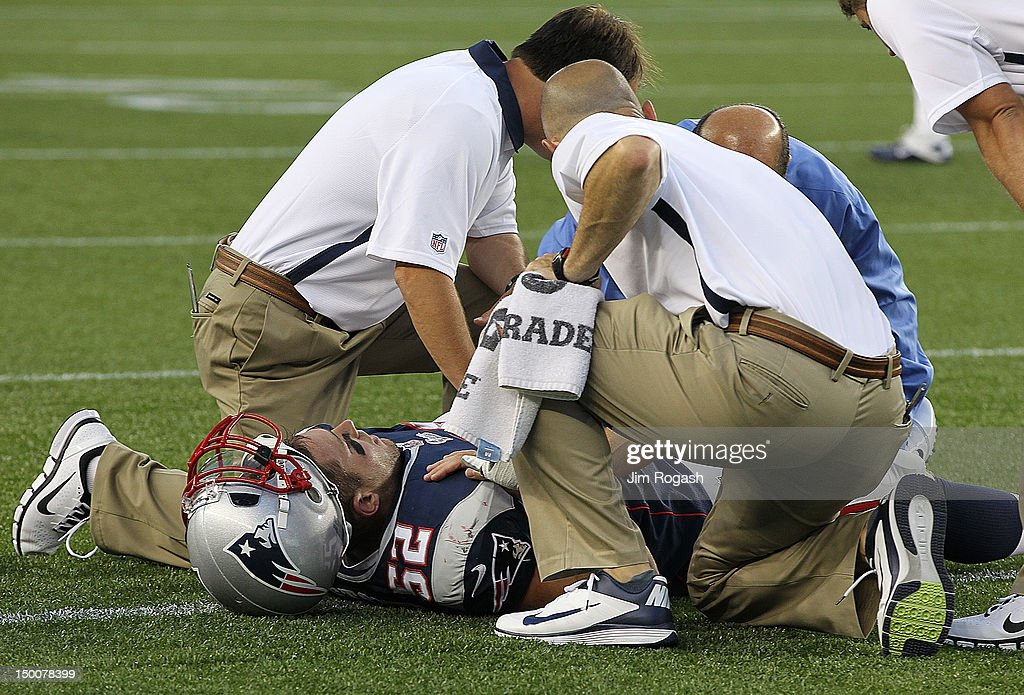 Dane Fletcher #52 of the New England Patriots is attended to by medical staff after he injured his knee in the first half against the New Orleans Saints at Gillette Stadium on August 9, 2012 in Foxboro, Massachusetts.